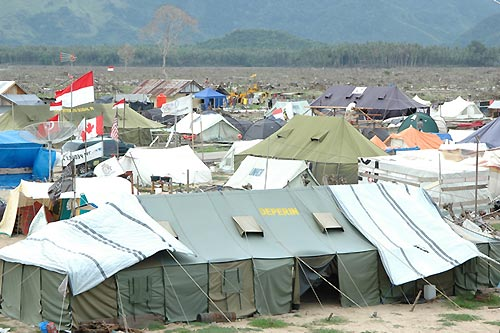 インドネシア・アチェ州の津波被災地。手前は救援機関などのテント。その向こうに広がる荒地のような所は漁村の跡。一望廃虚だった(撮影:筆者)