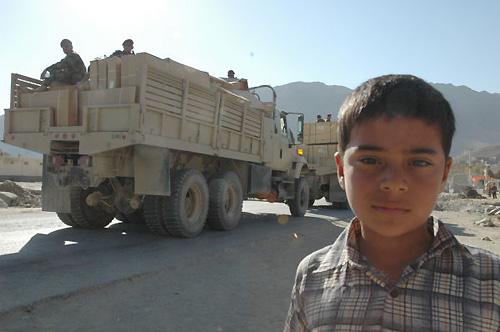 ゴルバッグ村の少年。後ろを行くのは国軍のトラック。